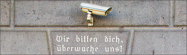 """Überwachungskamera an der Hausmauer mit der Schrift """"Wir bitten dich, überwache uns"""" darunter"""
